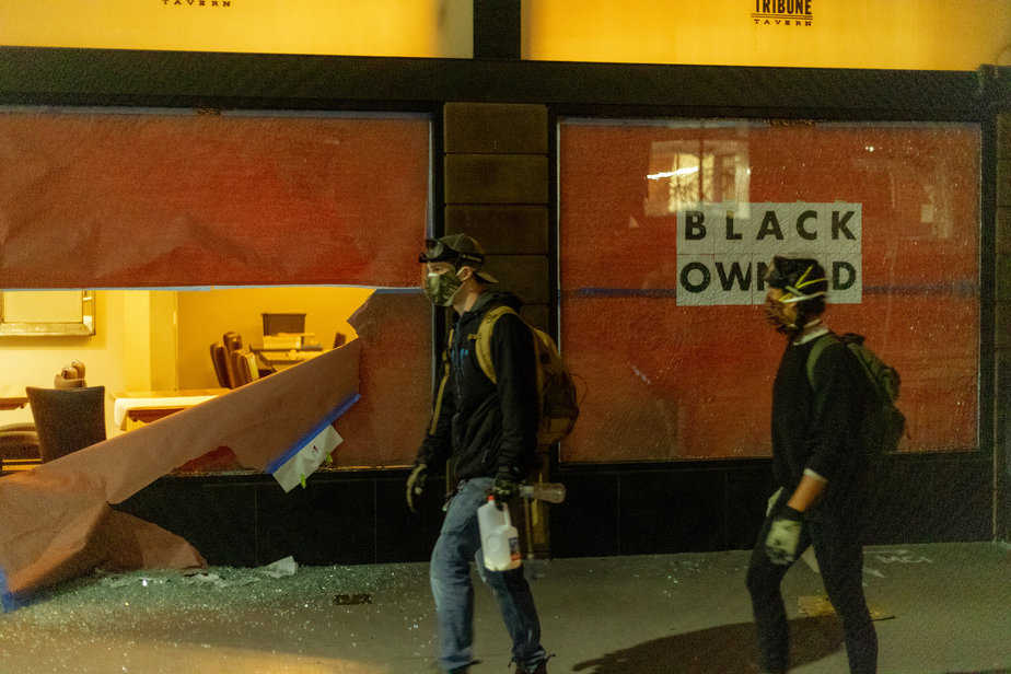 Onlooker protesters walking by a broken into Black-owned business in Oakland.
